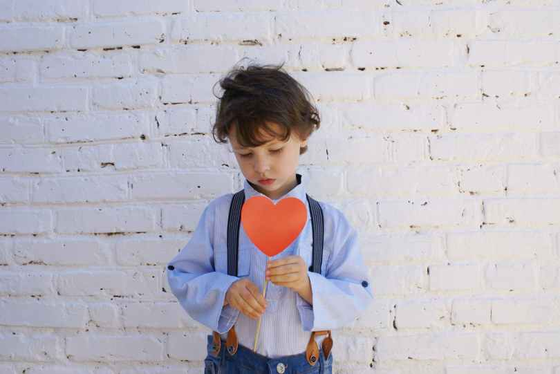 photo of boy holding heart shape paper on stick