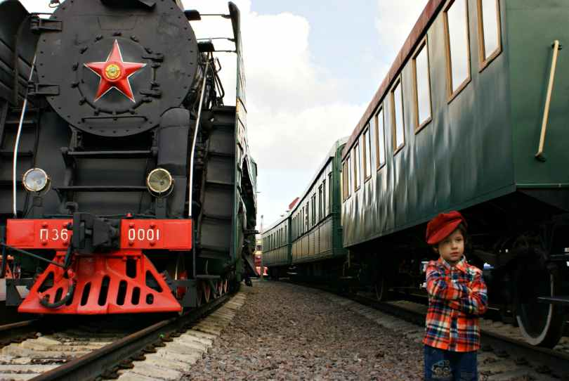 boy standing in between big trains