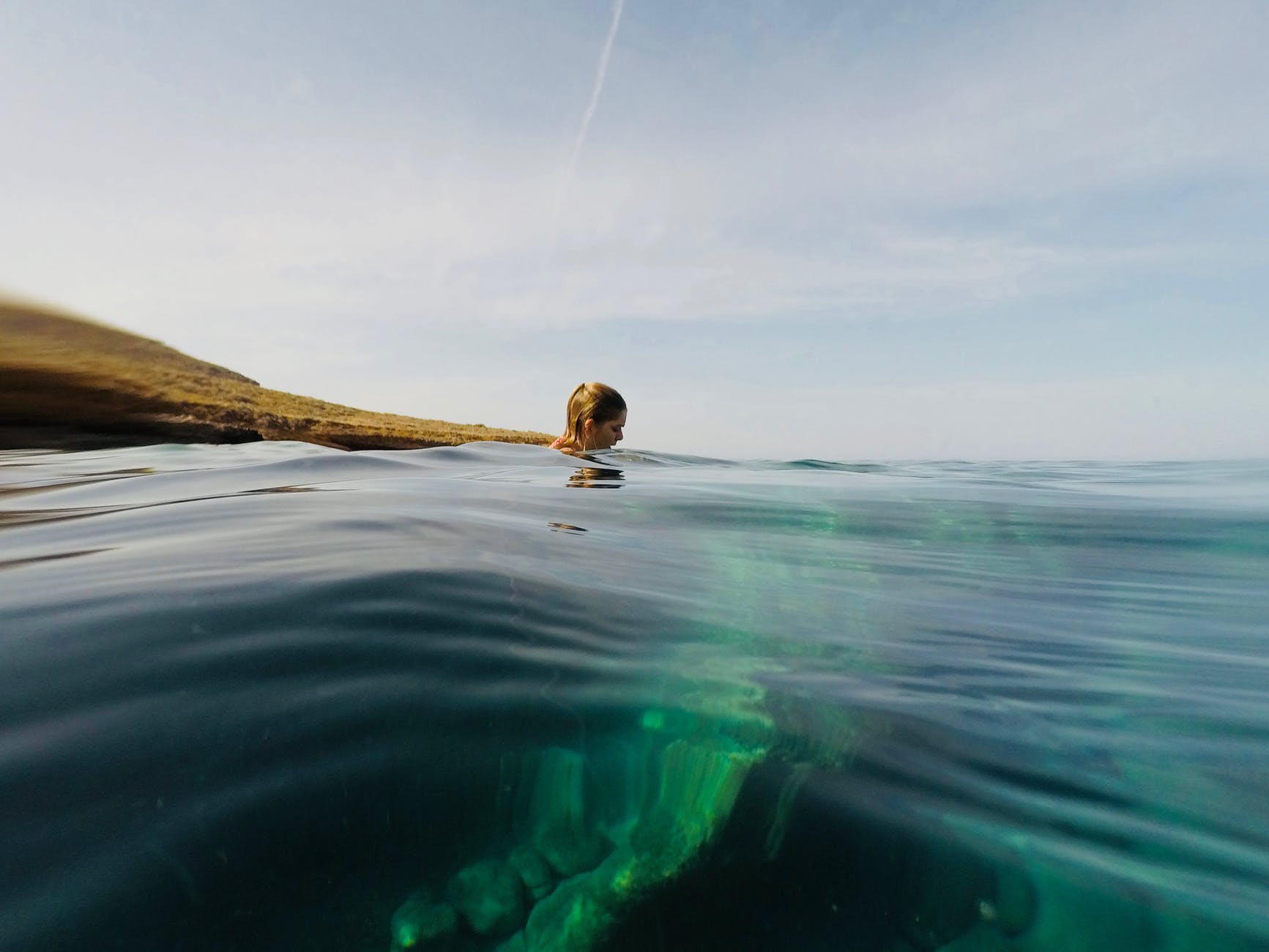 photo of woman swimming in ocean
