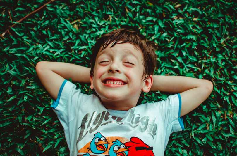 photo of boy laying on grass