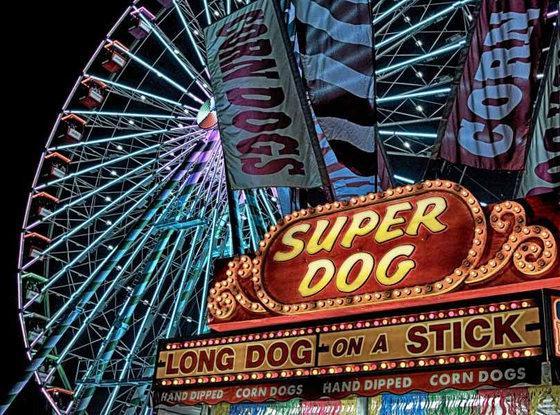 super dog hot dog food stall in front of ferris wheel during nighttime