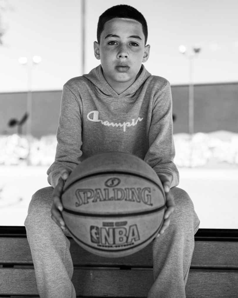a boy seated holding a basket ball
