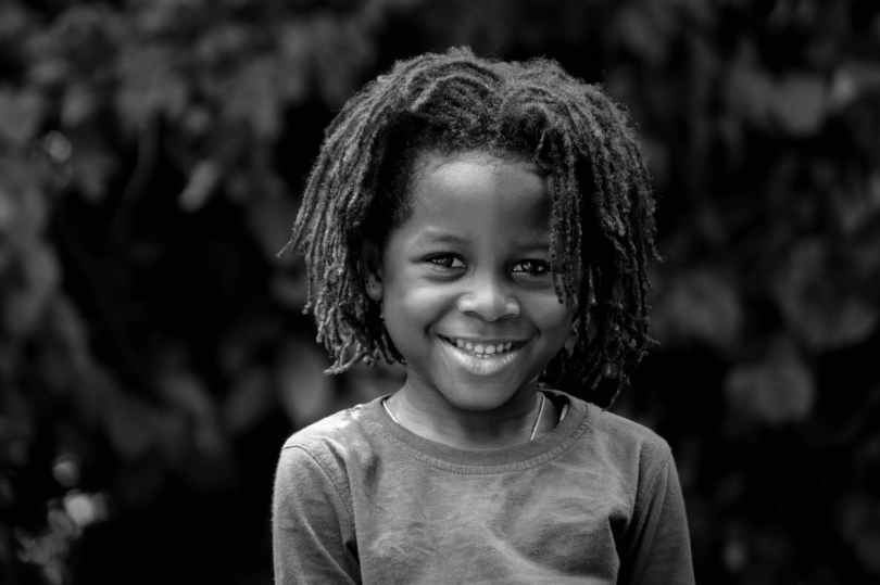 grayscale photo of toddler with braided hair